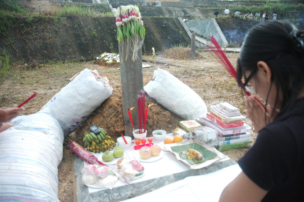 A girl performing Chinese offering ritual for deceased ancestor in front of a cemetery.